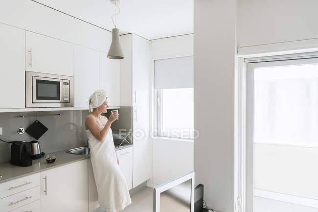 Заздрісна жінка має відсвіження з водою на зручній кухні. — стокове фото