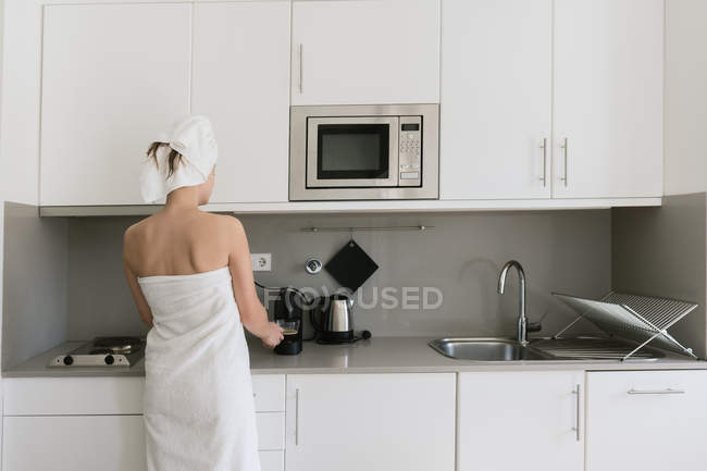 Back view of woman in white bath towels preparing beverage using coffee machine standing in modern comfortable kitchen — Stock Photo