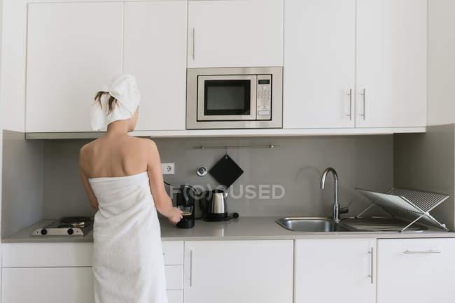 На задньому плані жінка в рушниках білої ванни готує напій за допомогою кавоварки, що стоїть на сучасній зручній кухні. — стокове фото