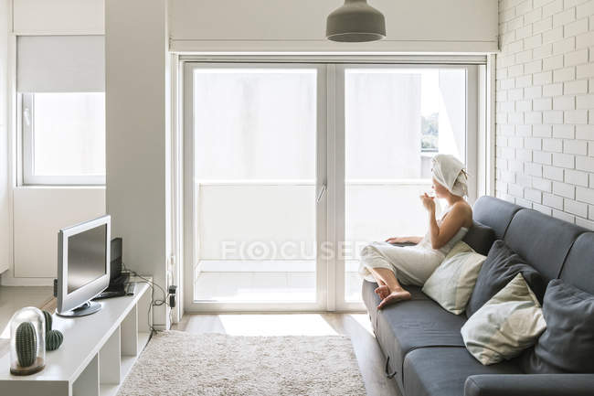 Adult relaxed woman enjoying life while resting on sofa and having hot drink after shower in own cozy apartment — Stock Photo