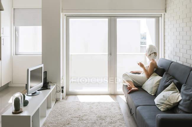Взрослая расслабленная женщина наслаждается жизнью, отдыхая на диване и принимая горячее питье после душа в собственной уютной квартире — стоковое фото