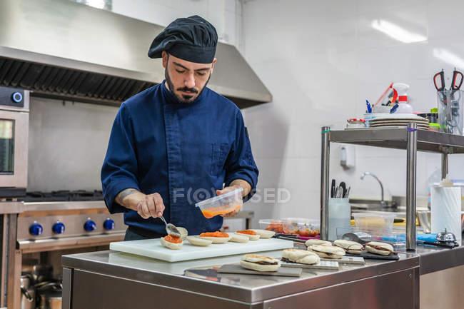 Повар в форме и шляпе готовит бутерброды с красной икрой, работая на кухне ресторана — стоковое фото