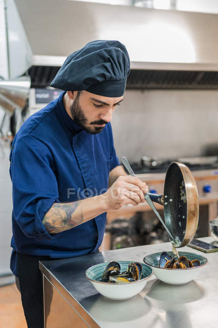 Cozinheiro masculino sério no prato de acabamento de chapéu preto e colocando ingredientes da frigideira em tigelas com mexilhões — Fotografia de Stock