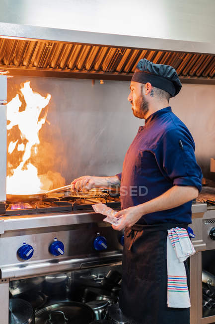Side view of male cook doing flambe on food while standing at gas stove and preparing dish in professional kitchen — Stock Photo