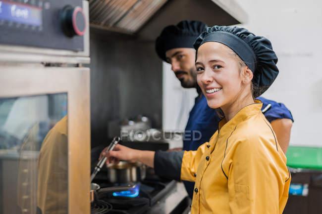 Chef profissional e assistente trabalhando na cozinha — Fotografia de Stock