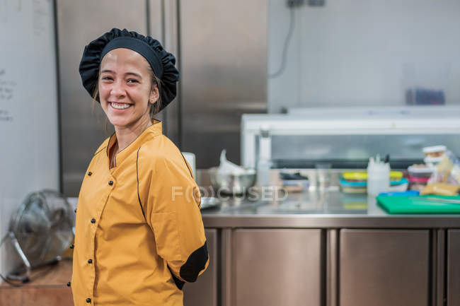 Cheerful young female chef in yellow uniform and black hat looking at camera while  standing in restaurant kitchen — Stock Photo