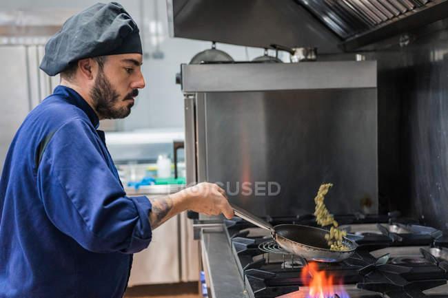 Шеф-повар жарит овощи на газовой плите — стоковое фото