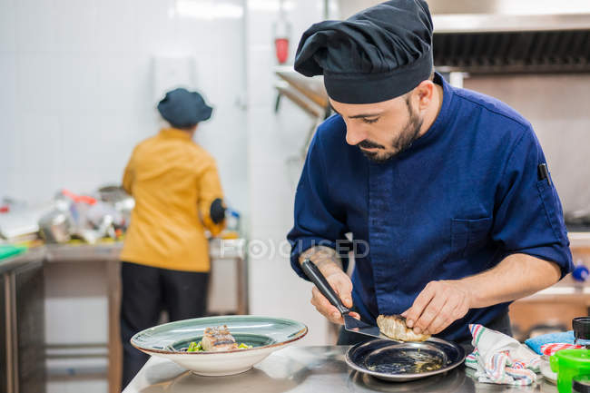 Cocinero masculino moderno sosteniendo espátula y sirviendo pescado en plato de porción mientras trabaja en cocina profesional con colega en el fondo - foto de stock