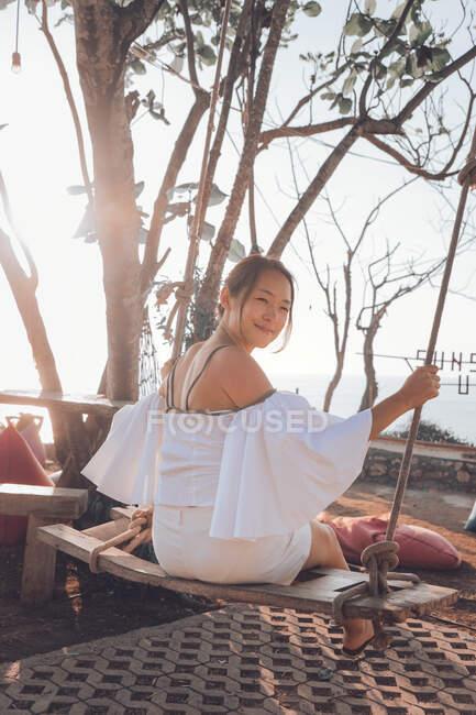 Mujer joven sentada en columpio - foto de stock
