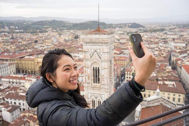 Glückliche asiatische Frau lächelt und macht ein Selfie mit dem Handy, während sie auf der Brunelleschi-Kuppel vor den alten Straßen von Florenz während einer Reise in Italien steht — Stockfoto