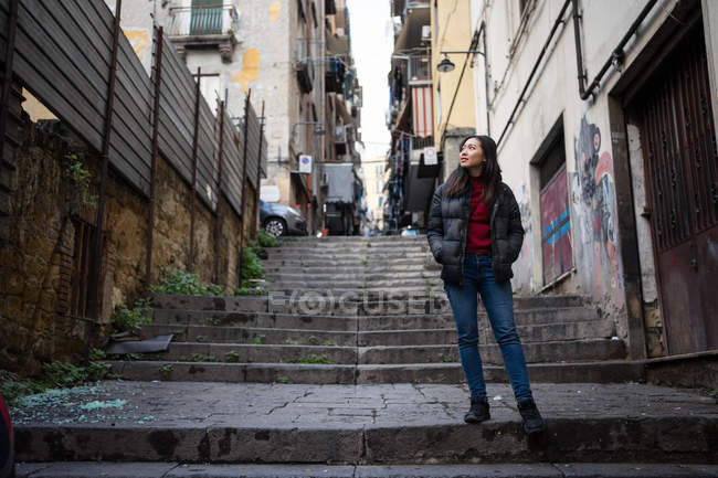 Mujer asiática con las manos en los bolsillos mirando hacia otro lado mientras está de pie en las escaleras fuera de los edificios resistidos en la calle de la ciudad - foto de stock