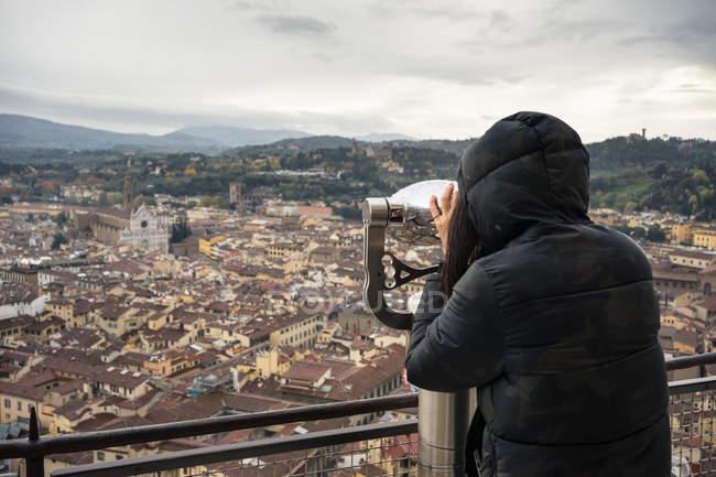Rückansicht einer Frau, die auf einer Aussichtsplattform in der Nähe der Brunelleschi-Kuppel in Italien mit einem Fernglas antike Straßen von Florenz erkundet — Stockfoto