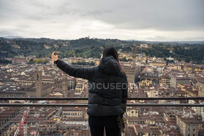 Rückansicht einer Frau, die ihr Smartphone benutzt, um ein Selfie zu machen, während sie auf der Aussichtsplattform der Kathedrale Santa Maria del Fiore in den alten Straßen von Florenz steht, Italien — Stockfoto