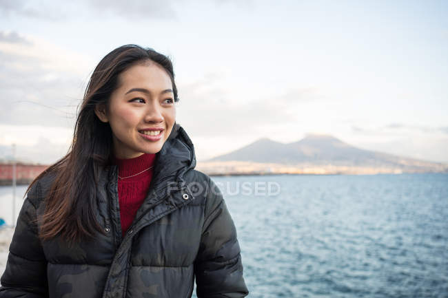 Satisfied resting woman in warm clothing enjoying view of beautiful on seashore at Naples at Italy — Stock Photo