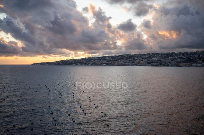 Mer tranquille avec ville sur la côte et ciel nuageux au coucher du soleil sur fond à Naples en Italie — Photo de stock