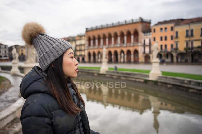 Vista laterale della giovane donna asiatica che riposa in abiti caldi e cappello passeggiando nel bellissimo parco Prato della Valle a Padova — Foto stock