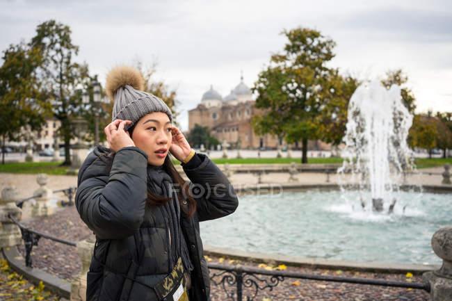 Vista laterale del viaggiatore dai capelli neri in abiti caldi e cappello passeggiando nel bellissimo vecchio parco Prato della Valle a Padova in Italia — Foto stock