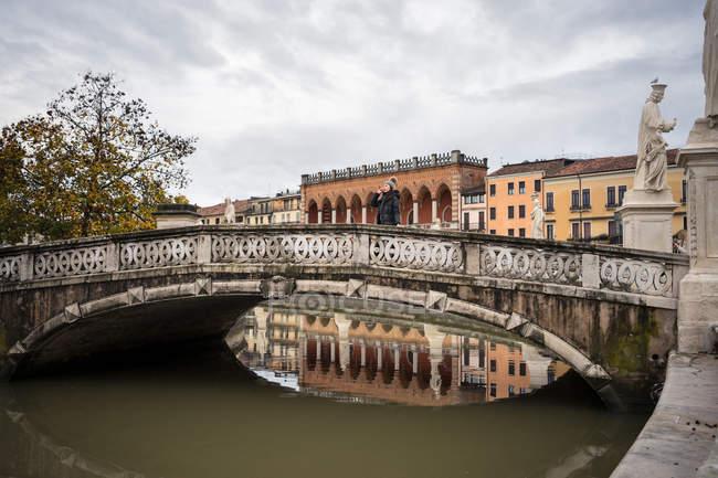 Turista in abiti caldi su un antico ponte a dondolo sopra lo stagno con vecchi edifici e statue sullo sfondo al parco Prato della Valle a Padova in Italia — Foto stock