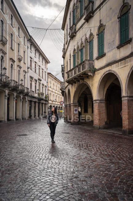 Viaggiatore femminile in abiti caldi passeggiando su strada in pietra a blocchi tra bellissimi edifici storici a Padova in Italia — Foto stock