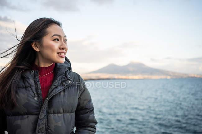 Удовлетворенная отдыхающая женщина в теплой одежде наслаждается видом на море в Неаполе в Италии — стоковое фото