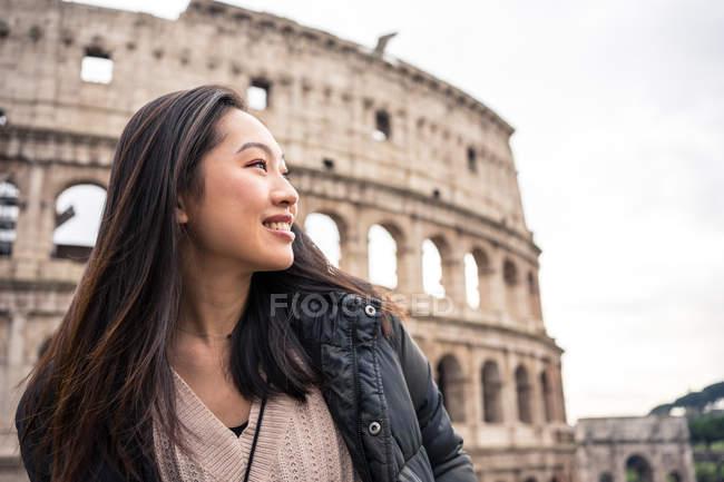 De baixo mulher feliz sorrindo e olhando para longe enquanto estava de pé no fundo borrado do Coliseu na rua de Roma, Itália — Fotografia de Stock