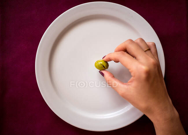 Faceless woman eating olive in restaurant — Stock Photo