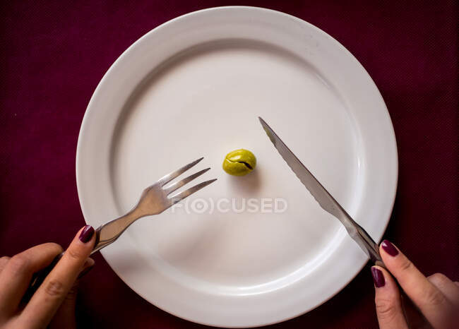 From above of crop female with knife and fork eating one green olive in restaurant of Malaga in Spain — Stock Photo