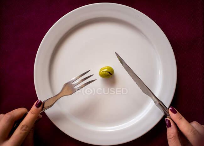Сверху урожая женщина с ножом и вилкой ест одну зеленую оливку в ресторане Малаги в Испании — стоковое фото