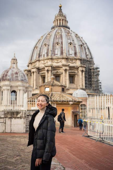 Agradável turista asiática em roupas quentes sorrindo e olhando para a câmera com a bela basílica de St Peters no Vaticano em Roma, no fundo — Fotografia de Stock
