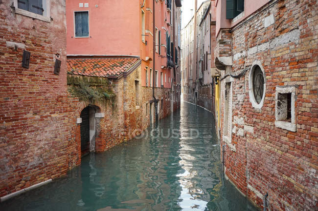 From above of narrow canal with turquoise water among brick colorful old buildings at city street — Stock Photo
