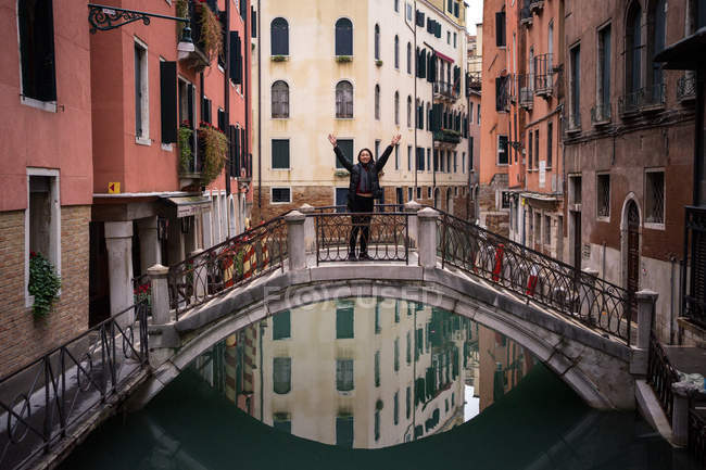 Content woman on vacation in warm clothing standing and raising hands on small bridge above water canal between old colorful buildings — Stock Photo