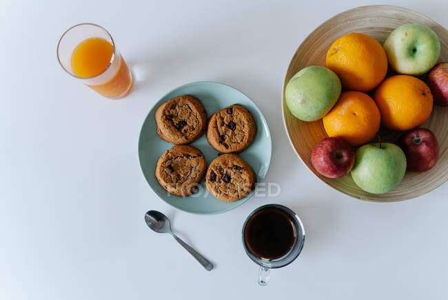Top view of tasty cookies and glasses with beverages and plate of fruits on white table — Stock Photo