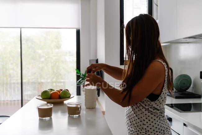 Bouteille d'ouverture féminine aux cheveux bruns avec du lait tout en faisant du café dans des tasses sur la table dans la cuisine moderne — Photo de stock