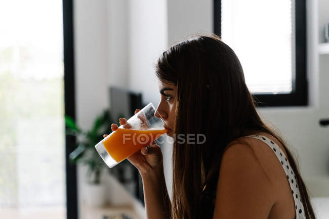 Side view of brown-haired woman drinking orange juice from glass and looking away at modern kitchen — Stock Photo
