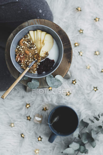 Top view of layout healthy organic meal with berry and apple and milk and muesli in bowl on cooking board near with cup of tea — стоковое фото