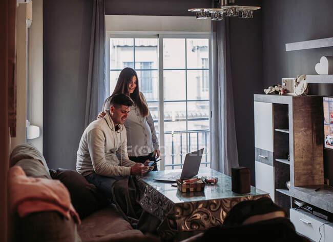 Пара ожидающих ребенка с помощью гаджетов дома — стоковое фото
