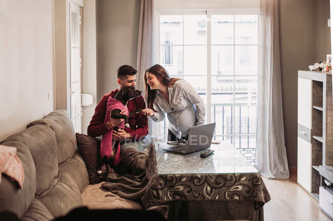 Young couple expecting baby having fun with dog at home — Stockfoto