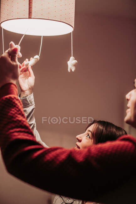 Expecting couple lighting chandelier in baby room — Stockfoto