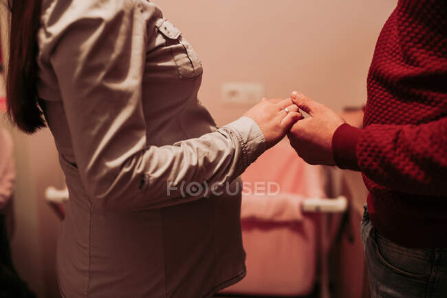Expecting couple holding hands in baby room — Stockfoto