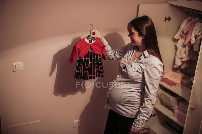 Happy pregnant woman holding cute little dress on hanger — Stockfoto