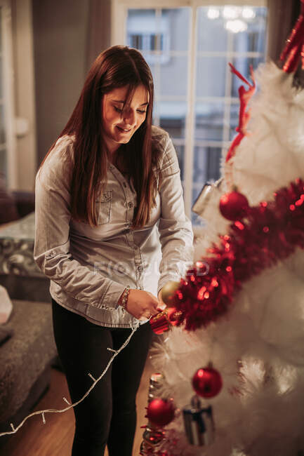 Pregnant woman arranging Christmas tree — Stockfoto