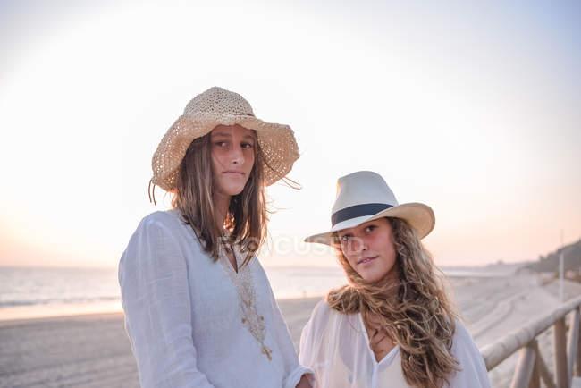 Copines souriantes dans des chapeaux parlant assis sur une clôture en bois sur la plage — Photo de stock