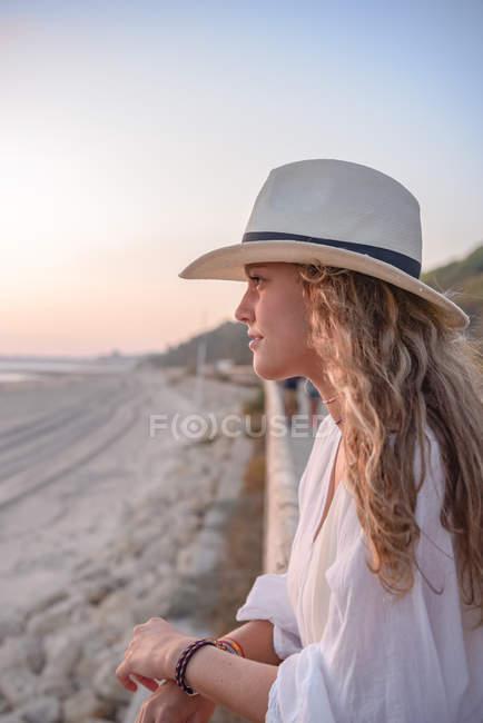 Вид сбоку симпатичной женщины с длинными кудрявыми волосами в шляпе, опирающейся на забор и отводящей взгляд в сторону — стоковое фото