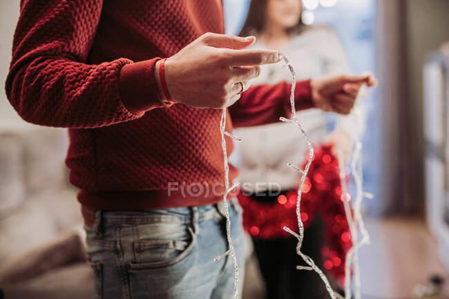 Молодая пара устраивает рождественскую елку дома — стоковое фото