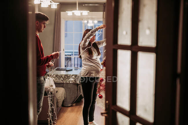 Young couple expecting baby arranging Christmas tree at home — Stockfoto