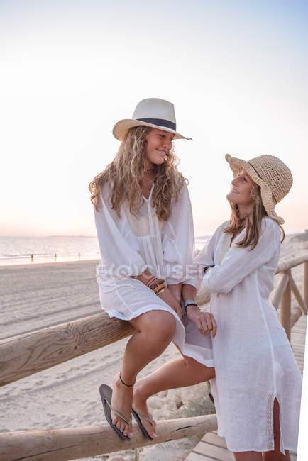 Charmante femme détendue en robes blanches et chapeau souriant tout en parlant placement confortable sur une clôture en bois sur une plage de sable fin par temps ensoleillé — Photo de stock