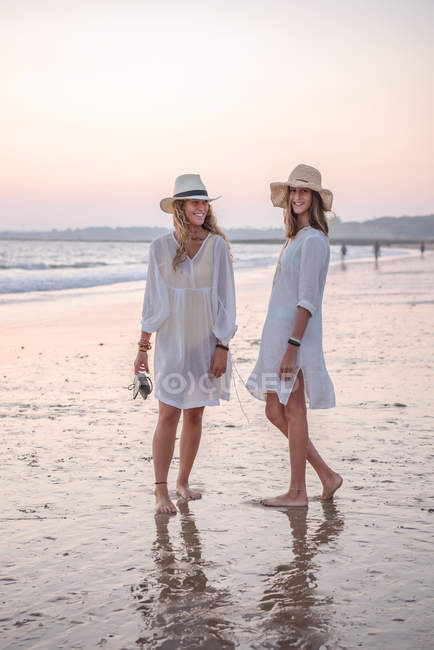 Graceful relaxed women in white dresses and hat smiling and looking at camera barefoot in water on beach in sunny day — Stock Photo