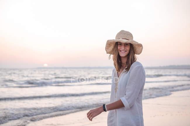 Affascinante donna in abito bianco chiaro sulla spiaggia ondulata — Foto stock