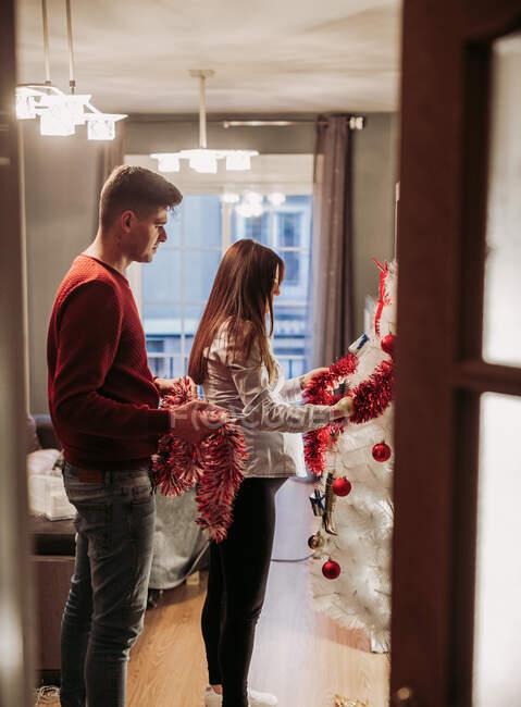 Молодая пара ждет ребенка, готовящего рождественскую елку дома — стоковое фото