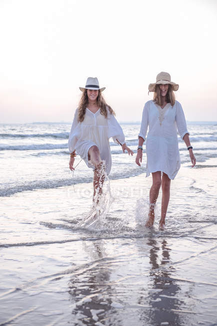 Smiling girlfriends in summer clothes barefoot in water on beach — Stock Photo